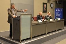 Ambasador Rumunii Ovidiu Dranga wygłasza wykład na mównicy. Przy stole prezydialnym siedzą od lewej: Przemysław Wyganowski i Grzegorz Korczyński.