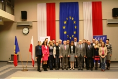 Zdjęcie grupowe na tle flag: Polskiej i UE.