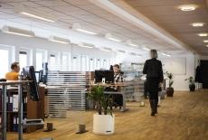 Biuro - otwarta przestrzeń, w której są ustawione biurka. Dwie osoby siedzą przy biurkacg, jedna osoba idzie przez biuro.