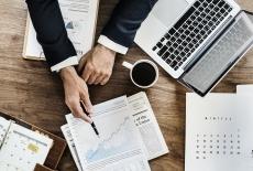 Dłoń trzymająca długopis wskazuje wykres na kartce papieru obok leży laptop i kubek z kawą