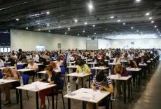 Uczestnicy egzaminu do postępowania kwalifikacyjnego w służbie cywilnej siedzią przy pojedynczych stolikach na hali egzaminacyjnej.