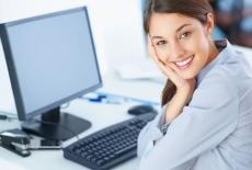 Uśmiechnięta kobieta siedzi przy biurku, na którym znajduje się monitor i klawiatura od komputera.