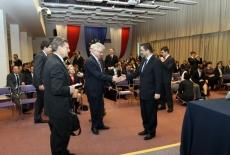 Widok na aule Dyrektor Jacek Czaputowicz wręcza dyplom jednemu z absolwentów, obok stoi Leszek Balcerowicz