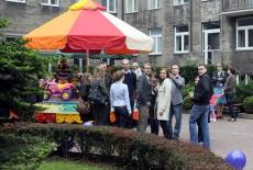 Zaproszeni goście na dziedzińcu KSAP stoją przy karuzeli