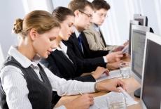 Czterech młodych ludze siedzi przed komputerami.