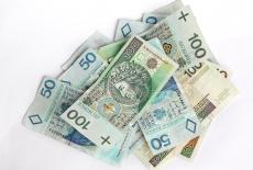 Na białym tle polskie banknoty.