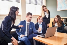 pięć osób siedzi na kanapach, patrzą w laptop stojący przed nimi na stole, dyskutują