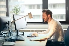 uśmiechnięty mężczyzna siedzi przed komputerem