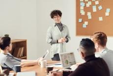 Sala szkoleniowa. Trzy osoby siedzą przy stole. Jedna kobieta stoi i mówi do osób siedzących. Na ścianie wisi tablica z przyczepionymi karteczkami.