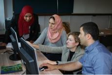 Przy komputerze prowadzący objaśnia trzem uczestnikom szkolenia