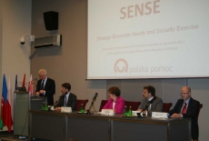 Dyrektor KSAP Jacek Czaputowicz stoi na mównicy i przemawia obok siedzą prowadzący szkolenie