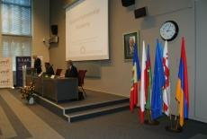 Dyrektor KSAP przemawia na mównicy, w rogu auli stoją na stojakach