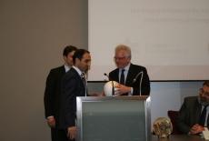 Dyrektor KSAP Jacek Czaputowicz stoi przy mównicy i wręcza upominek uczestnikom