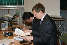 Dwóch prowadzących siedzi przy stole jeden z nich trzyma dokumenty drugi notuje