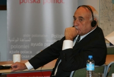 Jeden z urzędników siedzi przy ławce, ma słuchawki na uszach