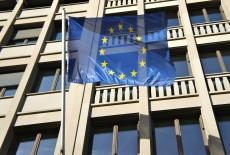 Flaga Unii Europejskiej powiewająca na zewntąrz przed budynkiem