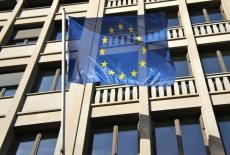 Flaga Unii Europejskiej powiewająca na zewnątrz przed budynkiem.
