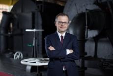 Absolwent KSAP Wojciech Chmielewski stoi w garniturze z założonymi rękami, w tle środek fabryki