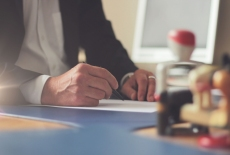 Mężczyzna siedzi przy stole, pisze na kartce. Na stole stoją pieczątki.