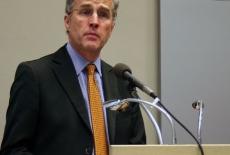 Pan Ambasador stoi przy mównicy i mówi do mikrofonu