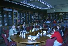 prof. Witold Mikułowski oraz goście spotkania siedzą przy stole w bibliotece KSAP