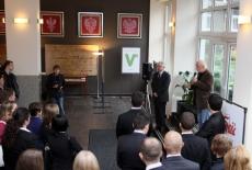 Pan Mirosław Chojecki stoi i mówi do mikrofonu do zgromadzonych gości, obok stoi Dyrektor KSAP