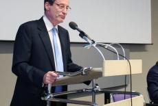 Ambasador Francji stoi przy mównicy i przemawia