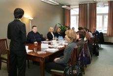 uczestnicy spotkania siedzą przy stole Pani prowadząca stoi i mówi