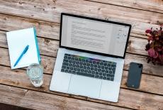 na drewnianym blacie stoi otwarty laptop, obok telefon, kartka, długopis, szklanka