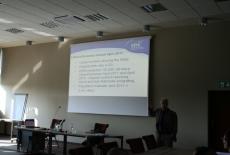 Pan James Connington stoi i prowadzi seminarium za nim wyświetlana jest prezentacja