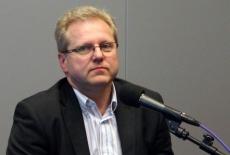 Pan Grzegorz Górski stoi przy mównicy i przemawia