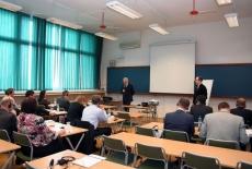 Sala wykładowa, uczestnicy szkolenia siedzą w ławkach, Dyrektor KSAP stoi i mówi do mikrofonu