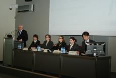 Prelegenci siedzą przy stole prezydialnym. Przy mównicy przemawia Dyrektor KSAP Jacek Czaputowicz