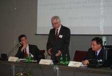 Dyrektor Ksap stoi przy stole prezydialnym i mówi do mikrofonu, obok siedzi dwóch Panów