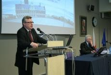 prof. Gaert Bouckaert stoi przy mównicy i przemawia, obok przy stole prezydialnym siedzi Dyrektor KSAP