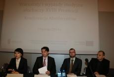 Osoby prowadzące konferencje siedza przy stole za nimi wyświetlana jest prezentacja