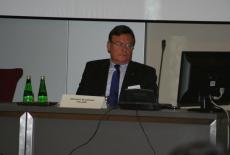 Sławomir Brodziński siedzi przy stole prezydialnym