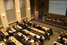 Widok na aulę i siedzących uczestników przy mównicy przemawia Pan