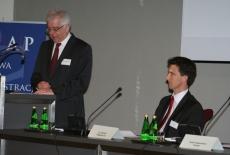 Dyrektor KSAP Jacek Czaputowicz stoi przy mównicy i przemawia, obok przy stole siedzi Pan