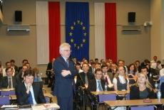 Dyrektor KSAP stoi między siedzącymi uczestnikami na auli i mówi do mikrofonu