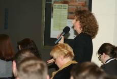 Uczestniczka konferencji stoi i mówi do mikrofonu. Obok siedzą inni uczestnicy