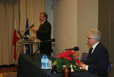 Bronisław Komorowski stoi na mównicy i przemawia obok siedzi przy stole Jacek Czaputowicz Dyrektor KSAP