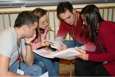Uczestnicy szkolenia siedzą w grupie 4 osób i dyskutują.