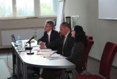 troje prowadzących siedzi przy stole z mikrofonami
