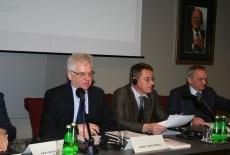 Dyrektor KSAP siedzi przy stole prezydialnym z innymi prowadzącymi