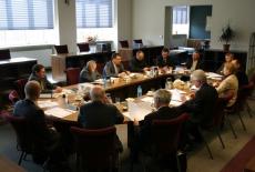 Uczestnicy posiedzenia Rady siedzą przy stole w bibliotece KSAP