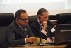 Dwóch panów siedzi ze słuchawkami na uszach, przeglądają dokumenty