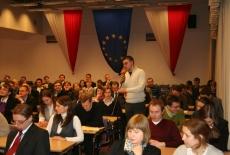 Uczestnicy spotkania siedzą w ławkach na auli jeden uczestnik stoi i mówi do mikrofonu