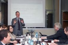 prof. Christopher Pollit stoi i przemawia za nim wyświetlana jest prezentacja