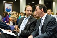 Ambasador siedzi na auli i rozmawia z Panem prowadzącym spotkanie